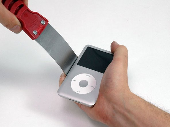 Image 1/1: Push with your fingers on the rear panel behind the putty knife to minimize bending. Slowly flex the putty knife, as shown in the picture, to ensure that most of the metal tabs on this side of the iPod are disengaged.