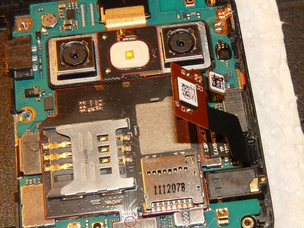 Remove the SIM and SD card board. You removed the pin next to the SD card tray already and you can see the glue on the board on this picture. Also remove the (whole!) pin between the cameras, circled in red.