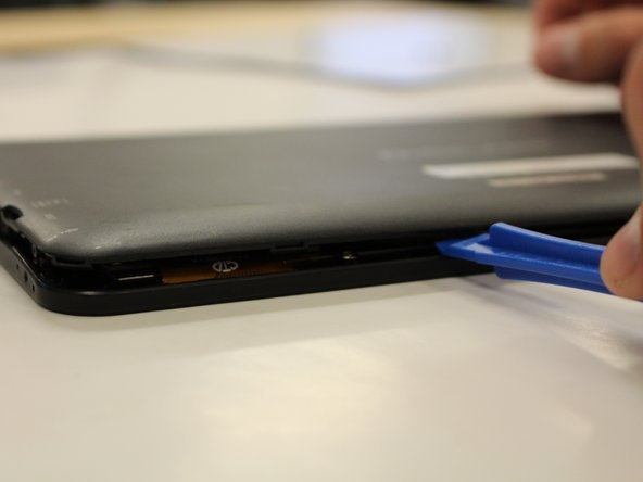 Image 2/2: Continue prying the edges while moving around the device's perimeter until the back can be easily removed.