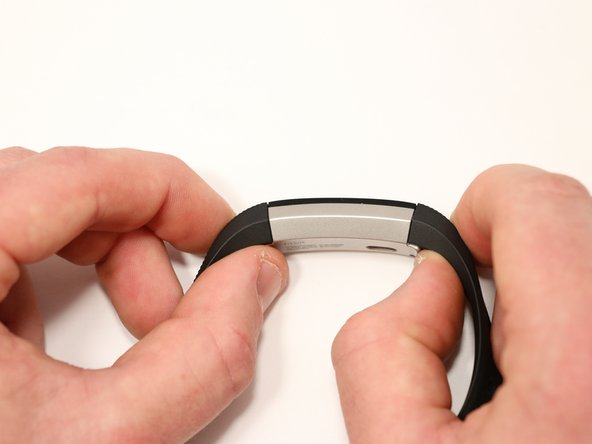 To release a latch, press down on the flat metal button holding the band to the Fitbit. Pull up on the latch to release the band from the body.