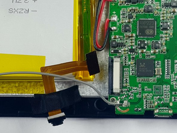 Carefully pull the ribbon cable out, removing the camera from the motherboard.