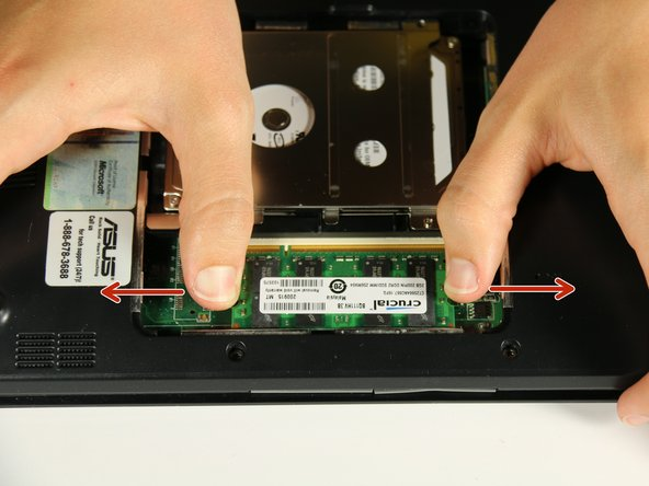 Push the metal bars on the sides of the RAM card to pull them out away from each other