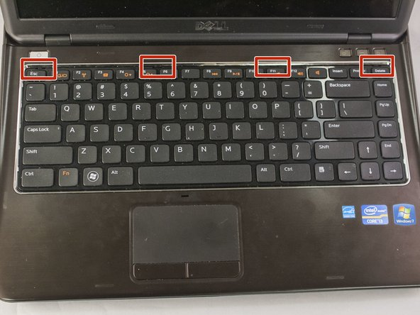 Image 1/3: Using a plastic opening tool, pry up on the four tabs holding the keyboard in place. Be careful not to damage the keys on the top of the keyboard. You will know when it has been successfully pried open when you hear four clicks from the top of keyboard.