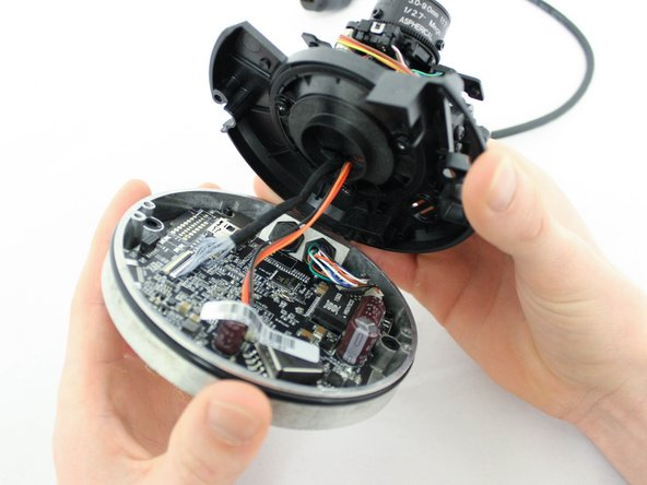Image 3/3: '''Be aware that cables are still connected under this base,''' and gently lift the plastic base with the camera away from the metal base with the motherboard.