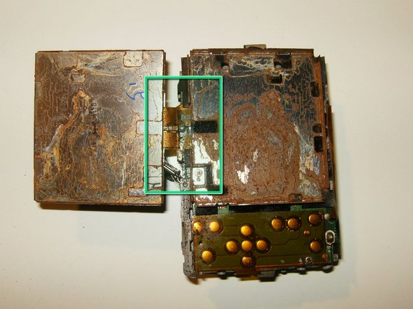 Once flipped over, the ribbon cable mounting underneath the LCD holder becomes visible. Extensive water damage is noted to the back frame of the LCD as well as corrosion on the LCD cable.