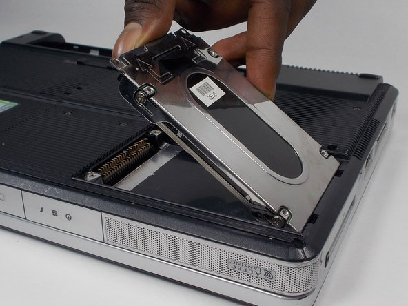 When reassembling: First, align the two tabs on the hard drive with the slots in the chassis, then press down on the left edge of the hard drive to seat the contacts.