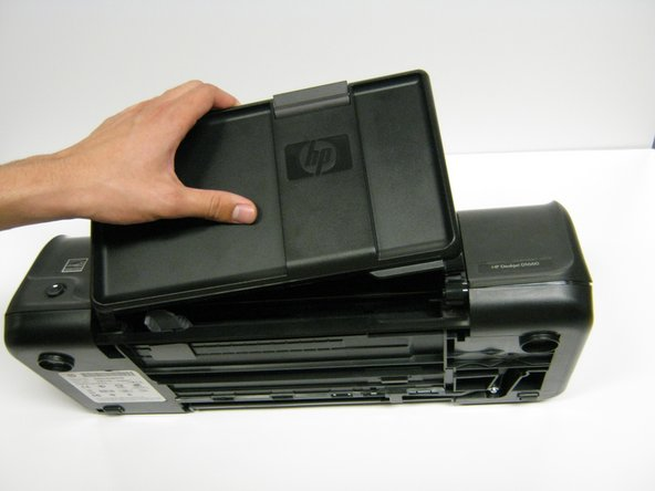 Image 1/1: Grab the paper tray by its right side and pull it to the left and up.