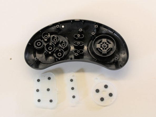 Use two fingers to remove each rubber membrane that rests on top of the buttons.