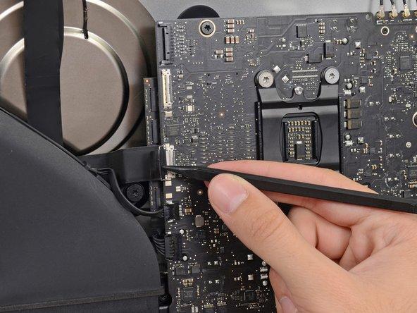 スパッジャーの先端を使って、カメラケーブルコネクタを基板に固定しているメタル製固定ブラケットを裏返します。