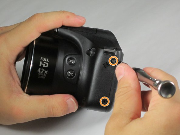 Image 2/3: Remove 4-4 mm screws on the left and right sides of the camera using a Phillips #000 screwdriver.