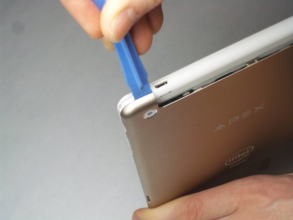 Start by bending the tablet back at the top white-colored portion to expose an opening between the back cover and the tablet body.