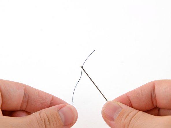 Infilare un'estremità del filo nella cruna dell'ago.