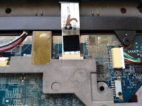 Antes de despegar el plástico alrededor del teclado, retira el cable de cinta que lo sostiene