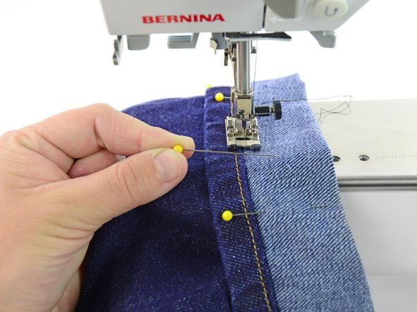Image 3/3: Continue sewing around the pant leg, at the edge of the hem, stopping to remove pins as you go.