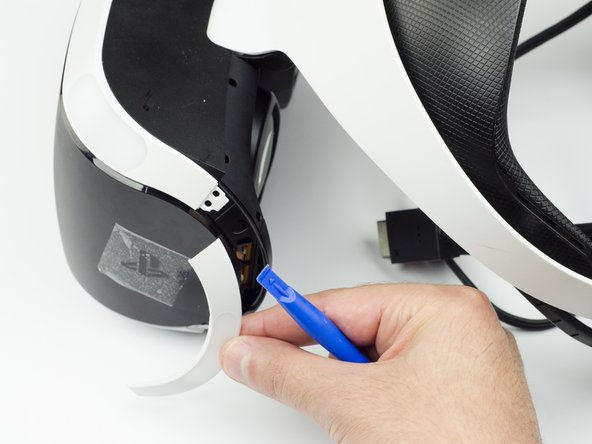 Using the plastic opening tool, carefully pry the white plastic panel free from the side of the headset. Repeat this action for the opposite side.