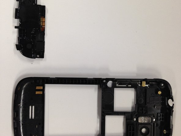 Find the back casing of the phone. Slide the plastic opening tool under the bottom of the speaker to pop it out.