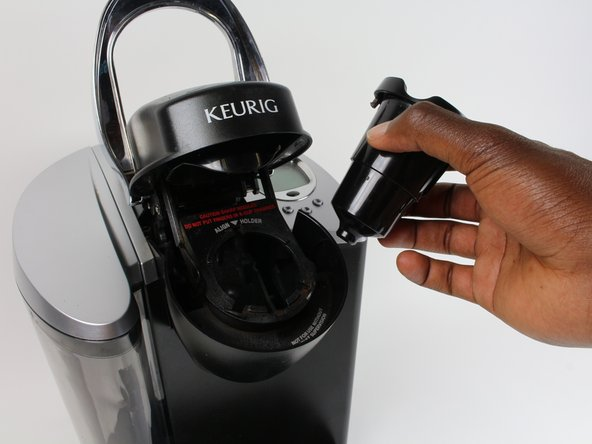 Remove K-Cup Pack Holder Assembly by pinching the left and right sides to release clamp. Wiggle slightly to remove