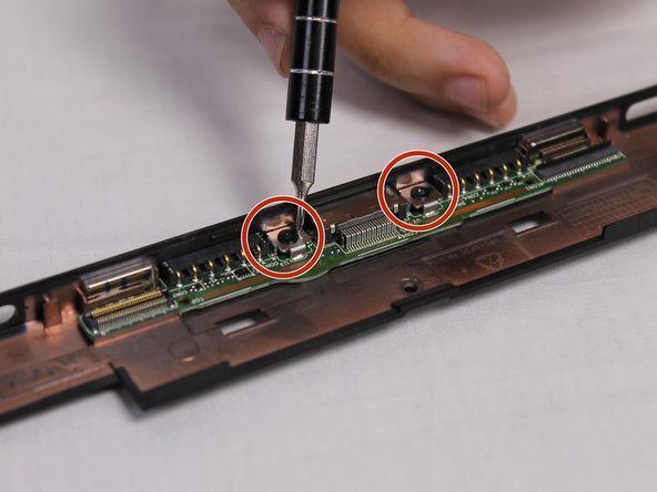 Now you must remove two 2.5mm screws that are securing the keyboard port to the frame.  When removing the screws use the Phillips #000 bit.