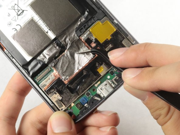 Peel the black tape off the lower part of the motherboard with a pair of tweezers.