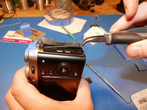 Image 3/3: Using a pair of pliers, pull the rod out of the top plate of the camera. Now you'll finally have access to all the screws that need to be removed.