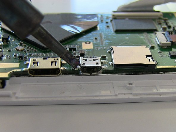 Work the iron on one prong at a time that is soldered to the motherboard. The USB port will release from the motherboard.