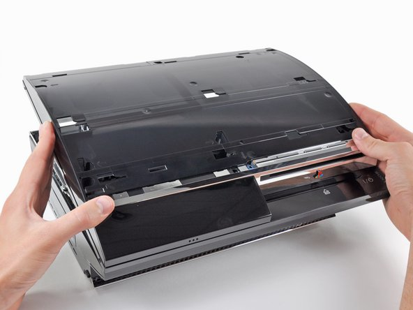 Image 1/1: Lift the top cover from its rear edge and rotate it toward the front of the PS3.
