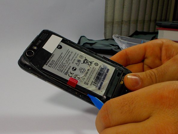 Image 1/3: Once the battery is loose, carefully lift from the bottom edge and remove the battery.