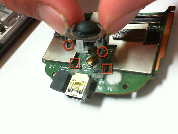 Insert a new trackball by guiding the prongs through the slots on the circuit board.