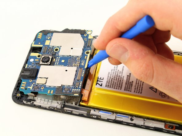 Wedge the plastic opening tool underneath the motherboard which is located at the top of the phone.