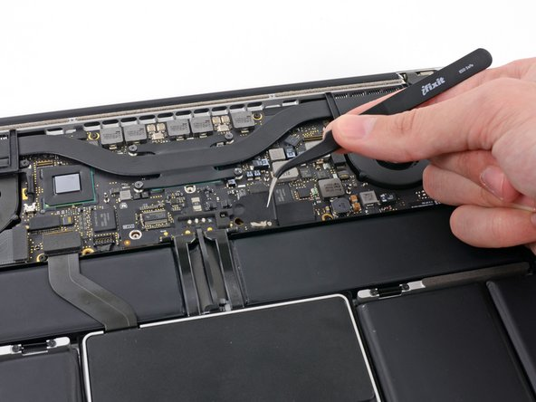 Use tweezers to remove the small plastic cover located near the bottom right of the battery connector board.
