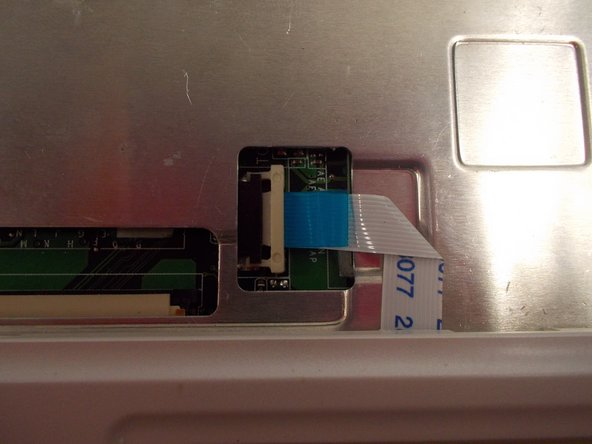 Image 2/2: The ribbon cable can now be pulled out using the blue tab attached to the cable.