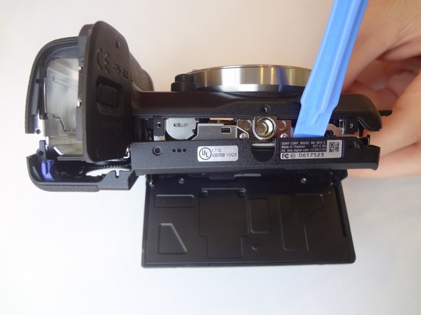 Image 1/2: Using a plastic opening tool, separate the bottom of the back case from the camera. Then proceed by separating the sides.