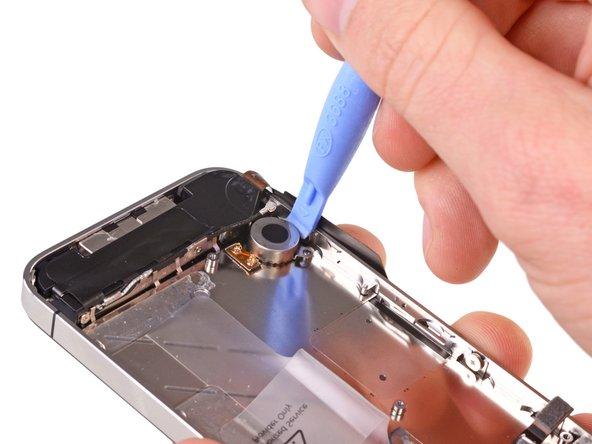 Используйте пластиковую лопатку для удаления вибромотора.