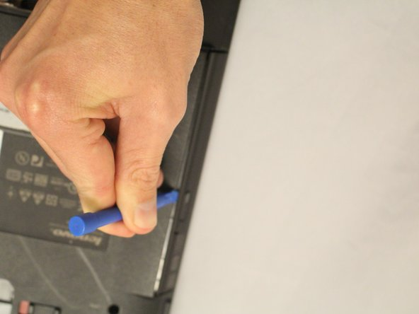 Pry CD-ROM drive from laptop using a plastic opening tool.