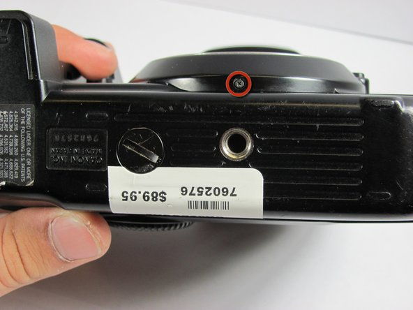 Flip the camera upside down and remove the 5.4mm screw below the lens bezel on the front of the camera.