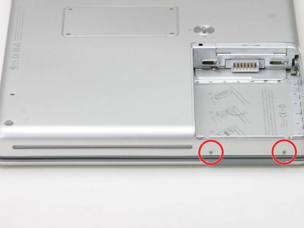 Image 1/1: Turn the computer 90 degrees clockwise just one more time, and remove the two Phillips screws on the exterior wall of the battery compartment.