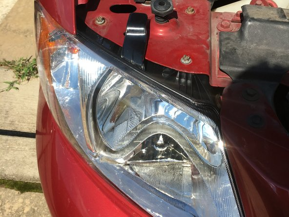 Image 1/1: Use the black handle, on top of the headlight, to help you align the holes to bolt the headlight in correctly. *Note* I screwed them in a little in a time clockwise to align it properly and not to cross thread the bolts.