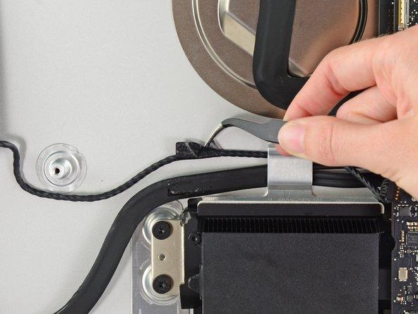 Si nécessaire, utilisez une pincette pour tirer sur le câble du haut-parleur gauche vers le haut et le dégager du clip de fixation derrière le boîtier arrière.