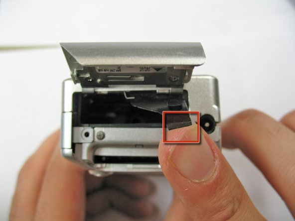 Open battery hatch and the black cover to expose the battery compartment.