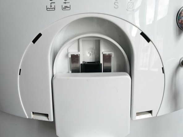 The image shows the machine after the front cover has been taken off. The four slots where the clips were are easily recognizable.