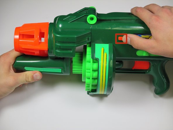 Image 1/2: Pull the orange slider towards the back of the gun while lifting up on the nose the gun.