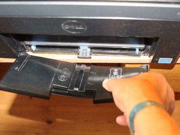 Entferne die ausklappbare Papierauflage, indem Du sie etwas biegst (vorsichtig) und an einer Seite dearrettierst.