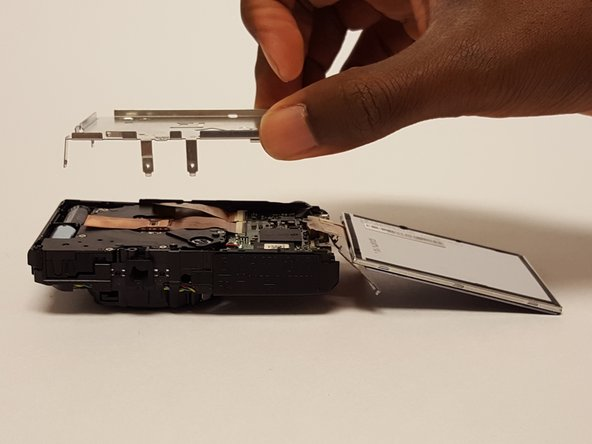 Once all of the screws are removed from the metal frame, gently lift up and remove the metal frame from camera.