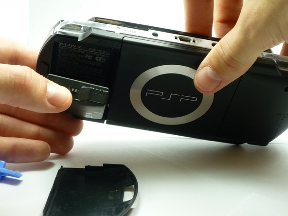 Image 1/2: Using your finger, remove the battery upwards from the system as shown.