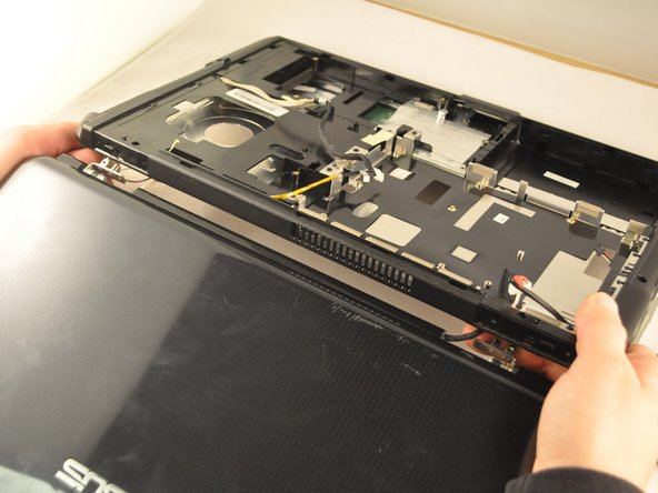 Be careful not to damage the cables that are attached to the screen frame. Be sure to pull them through the laptop carefully.