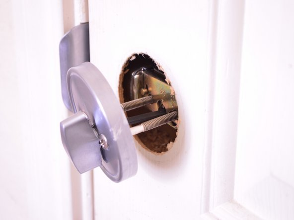 Take the lock cylinder and the 2.5 inch mounting screws  and insert them through the latch of the deadbolt.