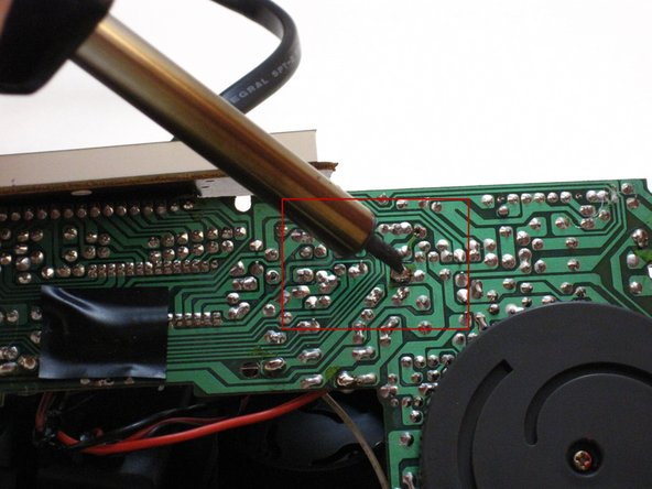 Apply the tip of the heated soldering iron to the DC- solder.
