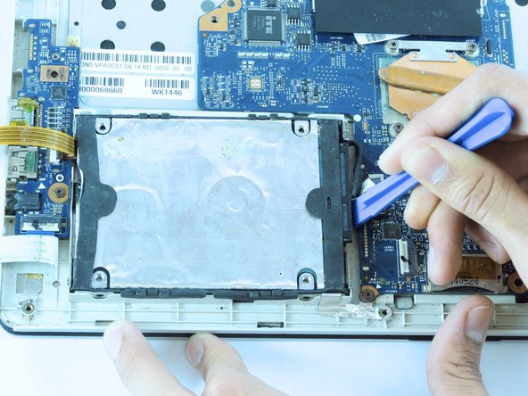 Use an opening tool or your fingers to lift the hard drive out of the laptop.