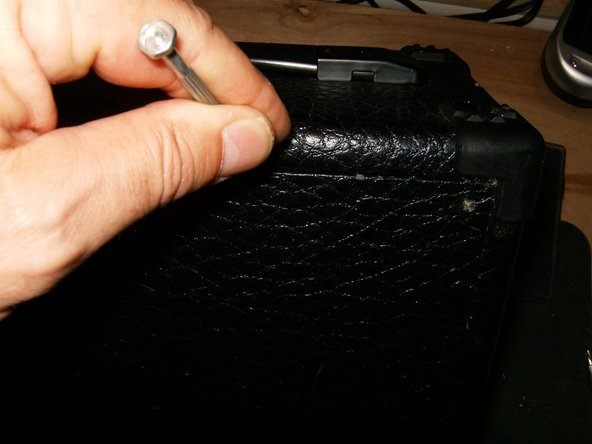 Remove the back panel. Use a small screwdriver, or other instrument to free it from its recess.