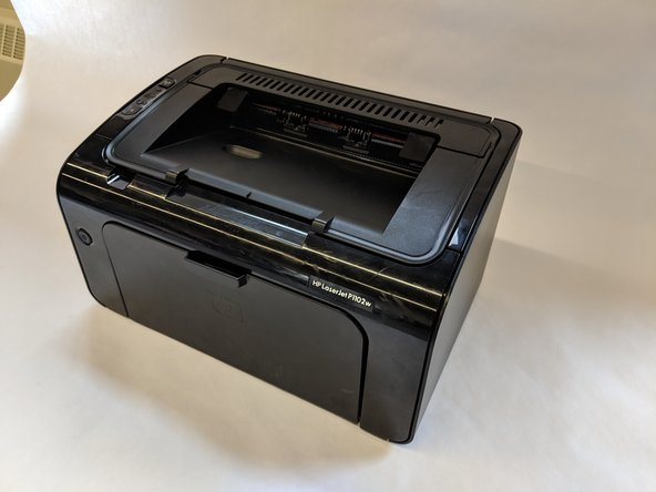 Flip printer on its back to expose the paper feeder housing.